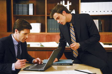 Business meeting - two businessmen in suits working together in boardroom photo