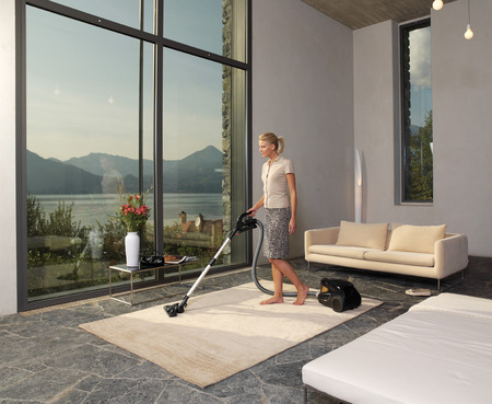 charlady: housewife with vacuum cleaner in a room