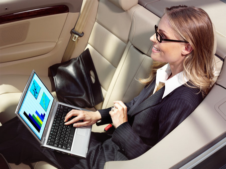 avocation: businesswoman has a fan with laptop in black car Stock Photo
