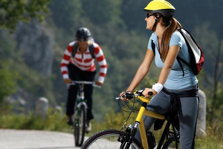 Beautiful happy women biking on road of countryside at summer