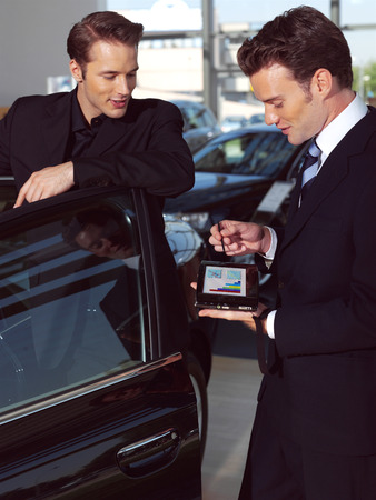 micro drive: Man buying a car in dealership sitting in his new auto, the salesman talking to him and explaining details