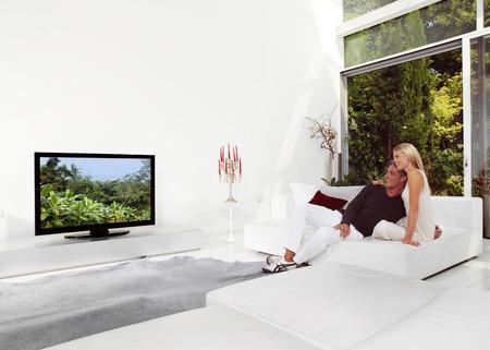 mujer viendo tv: Hermosa pareja sentada en el sofá viendo televisión