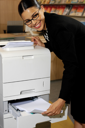 Pretty young businesswoman using Xerox machine at the office