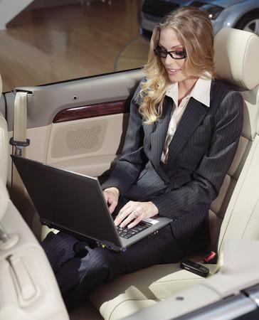 businesswoman has a fan with laptop in black car Reklamní fotografie