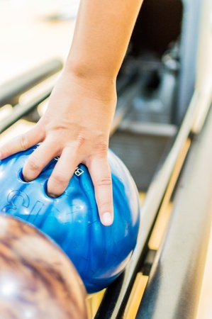 Holding ball against bowling alley. photo