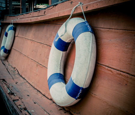 readily: lifebuoy blue stripes. attached to side of the ship. readily available. Stock Photo