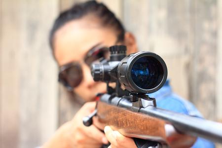 La femme au champ de tir a tiré d'un fusil. Banque d'images - 79973335