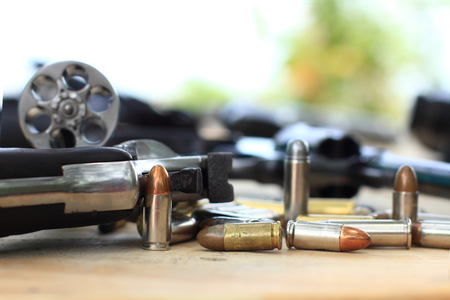pistol and bullet on table wooden