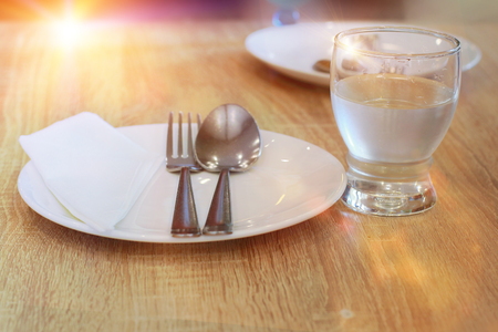 table top: set spoon and fork on dish for breakfast on table wooden in morning time