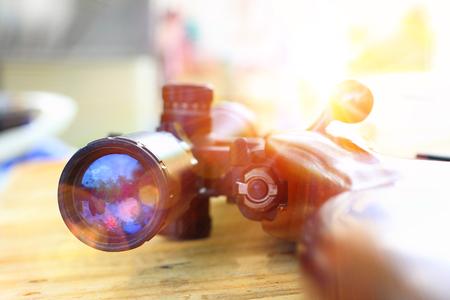 Primo piano del telescopio del fucile per la caccia sportiva sul tavolo in legno Archivio Fotografico - 85363824
