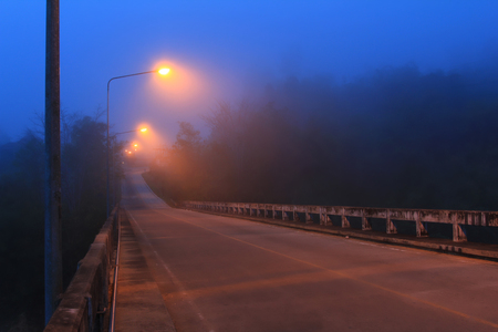 perspective landscape concrete road bridge with lamppost in night time and mist weather cold