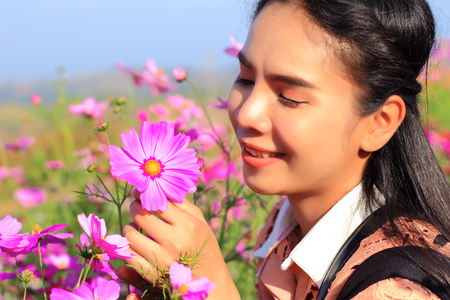 close up face,caucasian woman and expression happiness,pretty girl with pink comos flowers,woman wearing dress relaxing and happy with smelling flower in garden,female in park with on holiday Foto de archivo