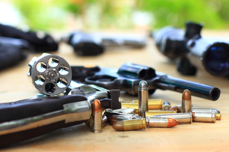 Close up group pistol with bullet on table wooden for outdoor sport and hunting,short gun semi automatic,hunting sport equipment Stock Photo