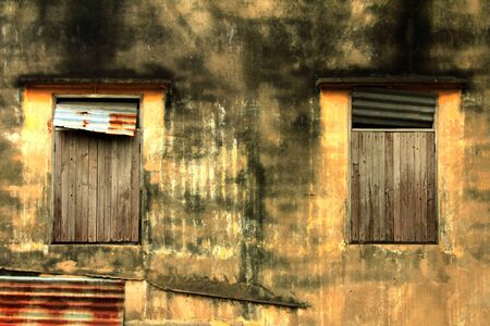 closeup of the yellow ancient wall of a house with an old window made of wood,antique of house and ruins