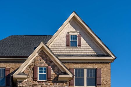 Double triangle gable with double hung sash window with complementing shutters, decorative arched trim, shake and shingle and architectural stone siding, brown eaves through system, fascia, soffit
