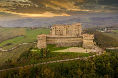 Aerial view of San Leo town and fortress used once as a prison on a rocky outcrop near the Adriatic sea resort Rimini and San Marino