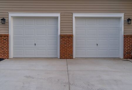 White electronic garage doors on a double garage driveway with beige horizontal lap vinyl siding and red brick accent on a new construction luxury American single family home in the East Coast USA