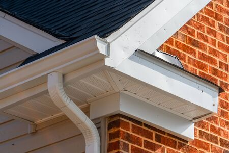 Closeup view of white gutter system with soffit vent, gutter guard, drop outlet, downspout, vinyl elbows, decorative trim molding, on the corner of a brick luxury house in America 版權商用圖片