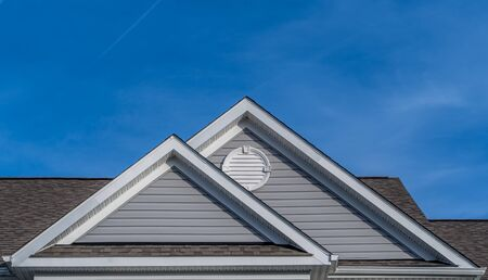 Reverse double gable close up on luxury single family residential home. White round louver vent. Roof line of traditional home with one gable running one way and reverse gables running the other.