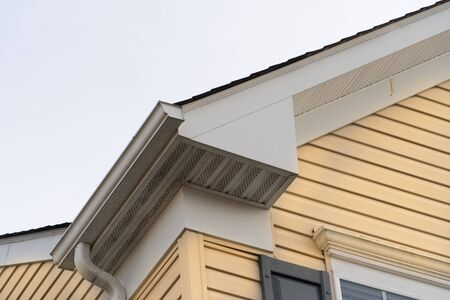 Horizontal vinyl siding, white frame gutter guard system, fascia, drip edge, soffit, on a pitched roof attic at a luxury American single family home neighborhood USA