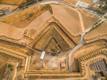 Elements of a fortification: aerial view of a triangle shape ravelin or demi lune with a redoubt in the ditch between 2 bastions in Almeida Portugal, structure adds additional defense to the gate