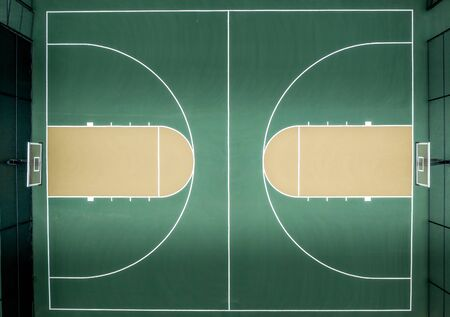 Aerial top down view of neighborhood multi-sport basketball court with green pavement, backboard, net, and jump circle highlighted, free throw lane, three point line, paint or key, hoop