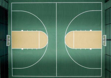 Vue aérienne de haut en bas du terrain de basket-ball multisports du quartier avec trottoir vert, panneau arrière, filet et cercle de saut en surbrillance, couloir de lancer franc, ligne à trois points, peinture ou clé, cerceau