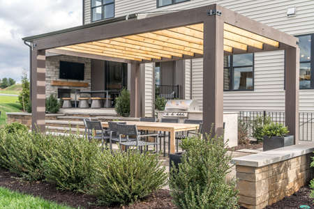 Trendy outdoor patio pergola shade structure, awning and patio roof, dining table, chairs, metal grill surrounded by landscaping
