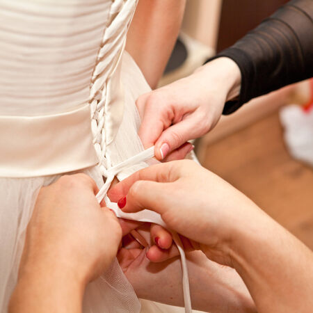 corset: tying corset bride closeup