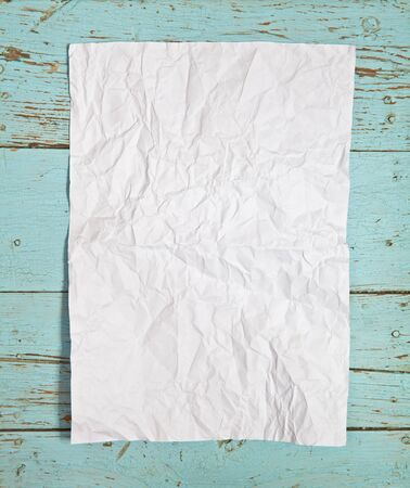 crumpled sheet: crumpled sheet of white paper on the wooden background Stock Photo