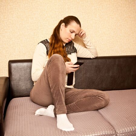 girl socks: young girl sitting on the couch and typing a message on your smartphone Stock Photo