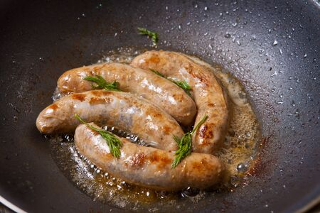 casings: sausages in natural casings are fried in a pan
