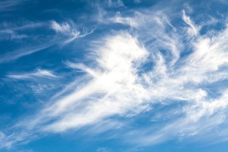 cirrus: White cirrus clouds against a blue sky background
