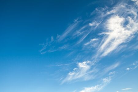 cirrus: White cirrus clouds against a blue sky background