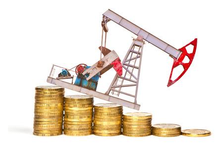 La bomba de aceite y la pila de monedas aisladas sobre fondo blanco. El concepto de la crisis del petróleo Foto de archivo - 44359385