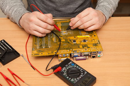 housing search: Master is looking for the fault of the motherboard with a multimeter.