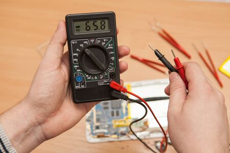 master: Multimeter in the hands of a master.
