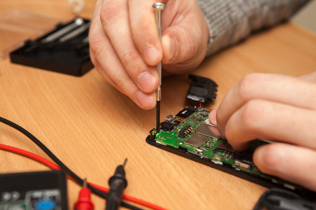 find fault: technician to disassemble the smartphone. Hands close-up.
