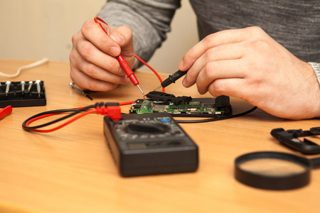 find fault: Technician looking for a fault in the phone with a multimeter. Stock Photo