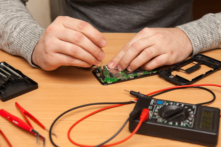 housing search: technician to disassemble the smartphone. Hands close-up
