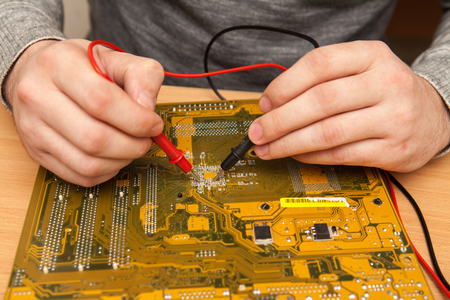 find fault: Master is looking for the fault of the motherboard with a multimeter.