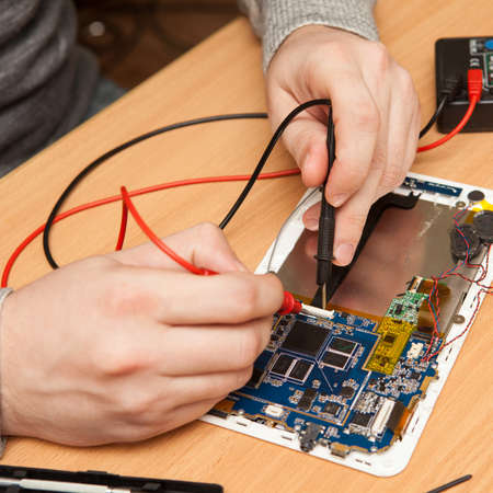 repairer: repairer is looking for damage to the tablet using a multimeter. Stock Photo