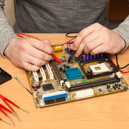 find fault: repairer is looking for the fault of the motherboard with a multimeter.