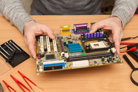 find fault: Technician holding the motherboard in the hands. Maintenance in the workshop. Stock Photo