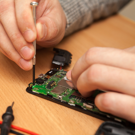 find fault: repairer to disassemble the smartphone. Hands close-up. Stock Photo
