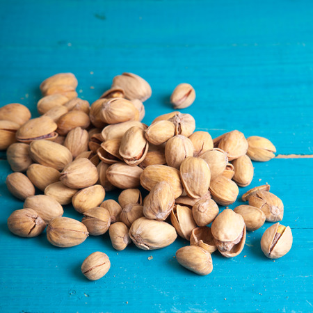 pistachios: salted pistachios on a blue wooden table Stock Photo