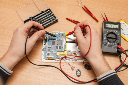 find fault: Master is looking for the fault of the tablet with a multimeter. Hands of a top view. Stock Photo