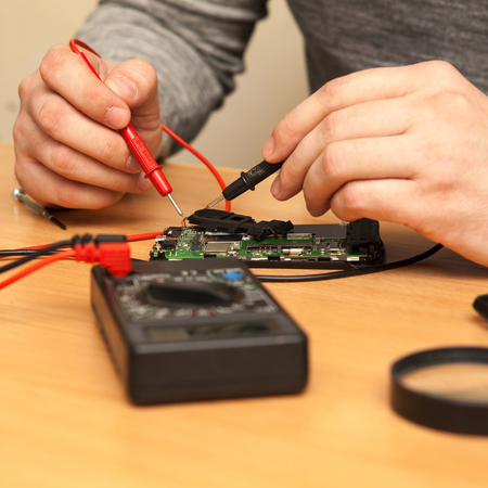 find fault: repairer looking for a fault in the phone with a multimeter.