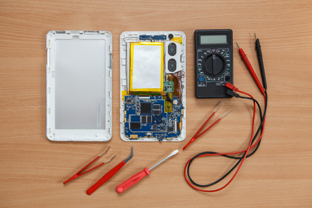 dismantled: disassembled tablet and tools on the table. View from above.