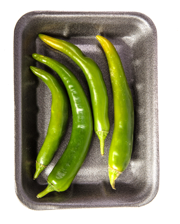 green chilli peppers in a plastic black tray. on a white Archivio Fotografico